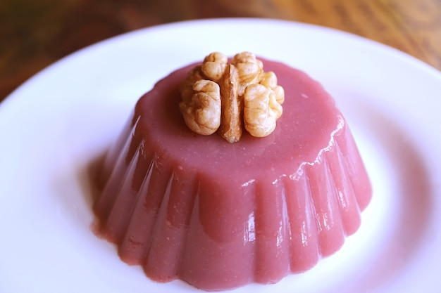 Plate of pelamushi topped with walnut, a popular georgian dessert made with grape juice