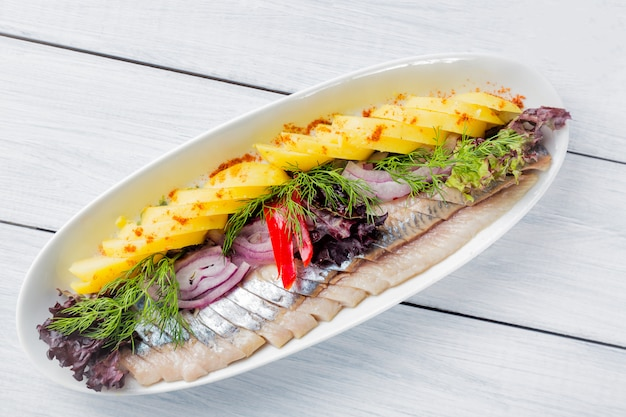 Plate of pieces of herring with fried potato,onion, pepper and herbs on white plate and wooden table