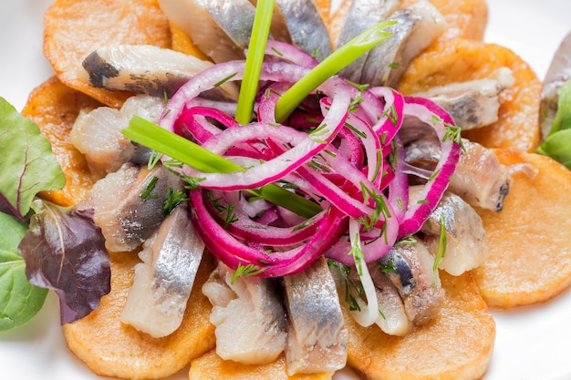 Plate of pieces of herring with fried potato, onion and salad