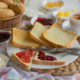 A plate of plain square toast slices and triangular toasts with jam