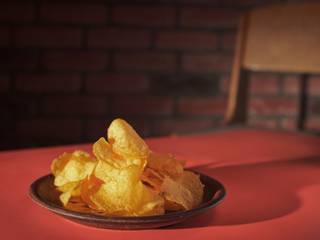 A plate of potato chips on a red table