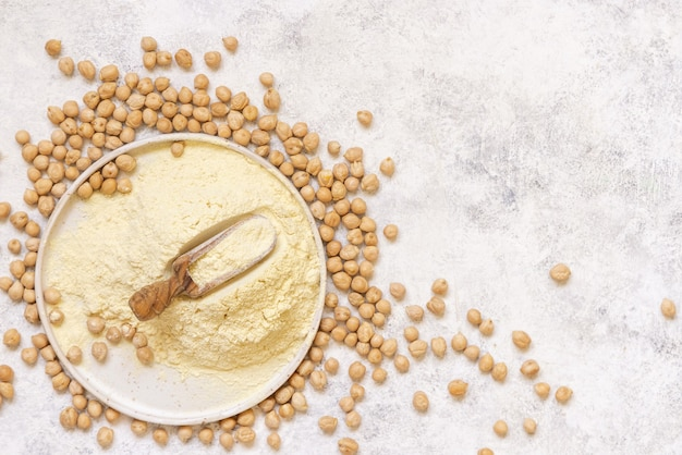 Plate of raw chickpea flour and beans on white table top view