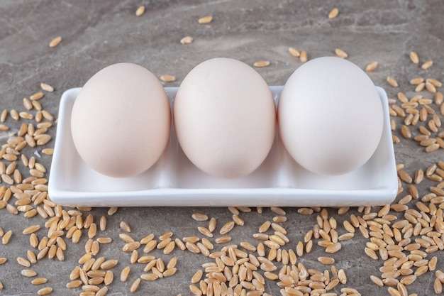 Plate of raw eggs and barley on marble background.