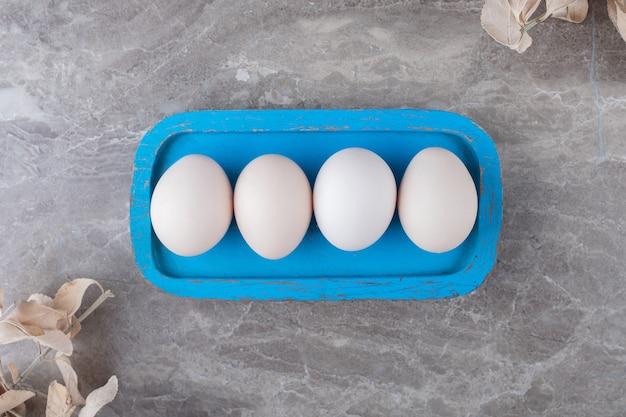 Piatto di uova crude su sfondo marmo.