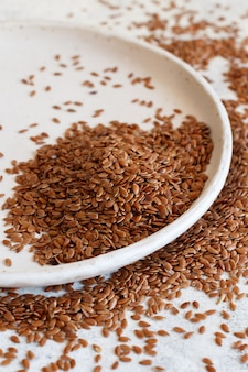 Plate of raw flax seeds  close up