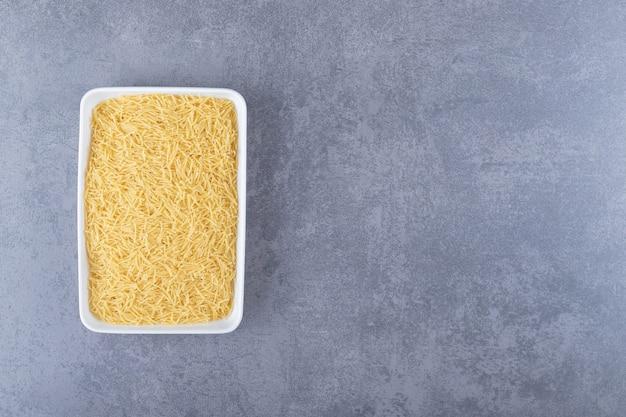 Plate of raw macaroni on stone background.