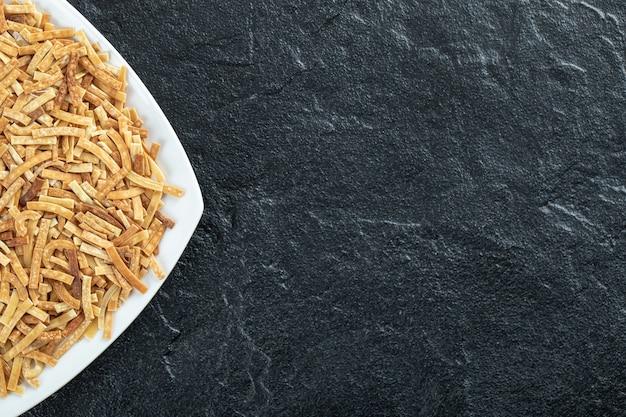 Piatto di pasta cruda su sfondo scuro. foto di alta qualità