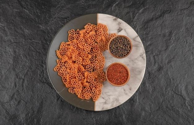 Un piatto di pasta cruda a forma di cuore con pepe su tavola nera