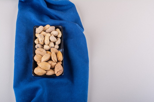 Plate of raw shelled almonds and peanuts on blue cloth. high quality photo