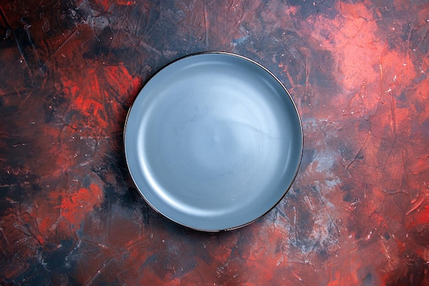 Plate on the red-blue background blue round plate