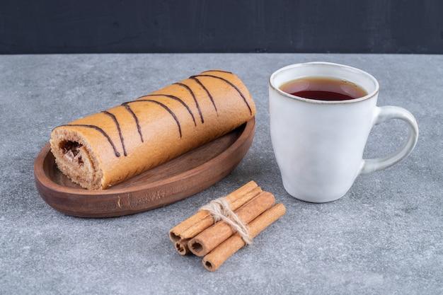 Piatto di torta arrotolata, tazza di tè e bastoncini di cannella sulla superficie di marmo