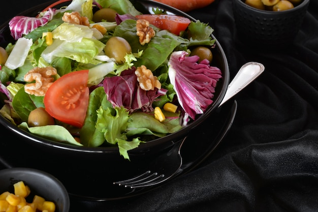 Plate of salad with lettuce, tomato, olives and oil. on a black cloth