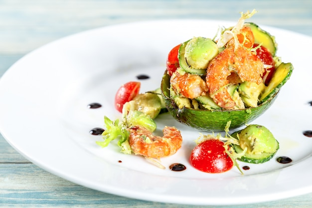 Plate of salad with shrimps, avocado and tomatos