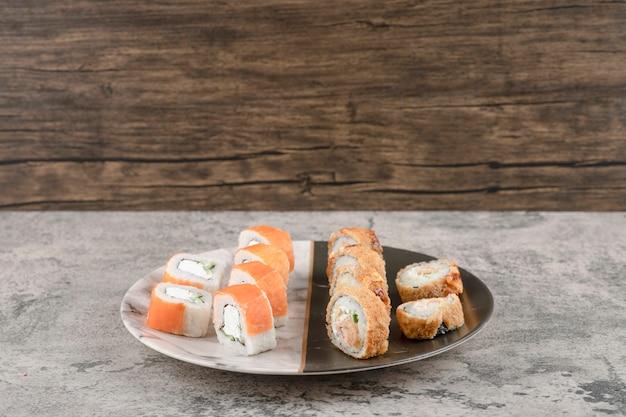 Piatto di salmone e involtini di sushi caldi posti su un tavolo di marmo
