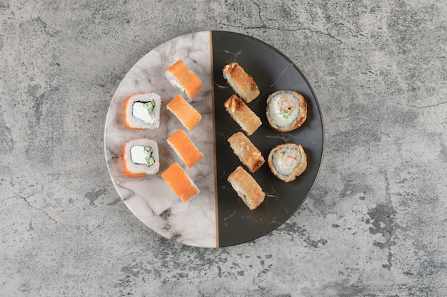 Plate of salmon and hot sushi rolls placed on marble table