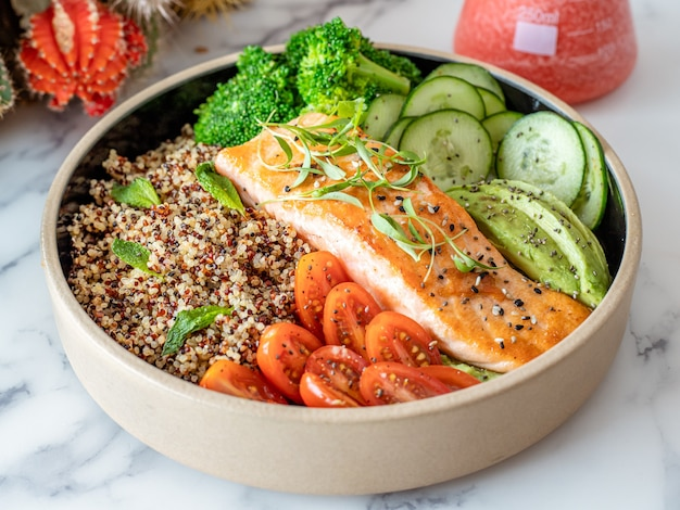Plate of salmon with quinoa and raw vegetables
