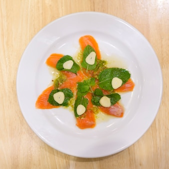 A plate of salmon with spicy seafood sauce on wooden table