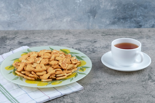 Plate of salted crackers and cup of hot tea on marble background.