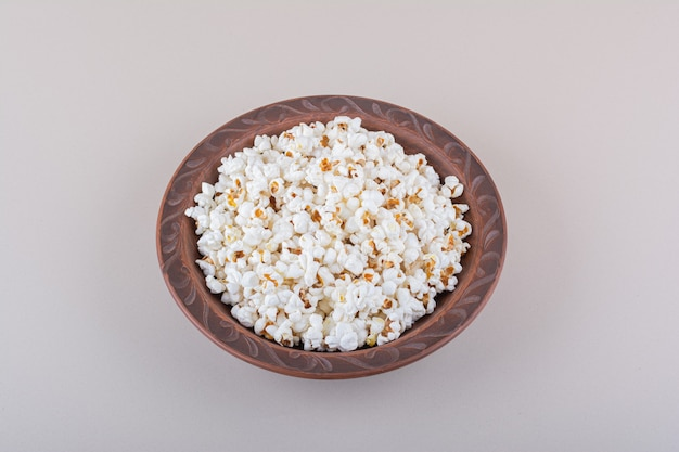 Plate of salted popcorn for movie night on white surface. high quality photo