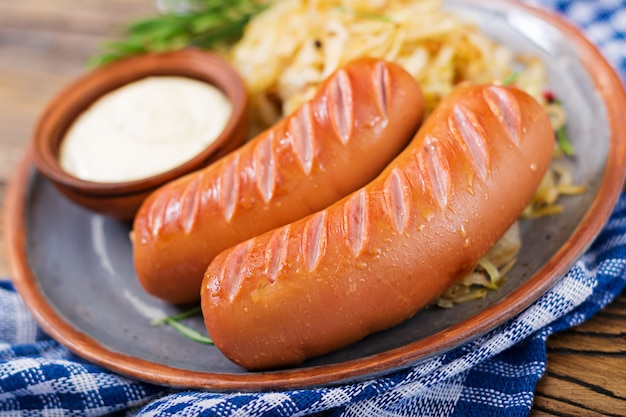 Plate of sausages and sauerkraut on wooden table. traditional oktoberfest menu
