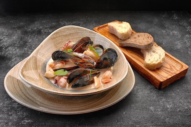 A plate of seafood, scallops, mussels, shrimps, squids, in sauce, with croutons, bread, on a wooden board