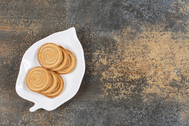 Piatto di biscotti ai semi di sesamo sul tavolo di marmo.