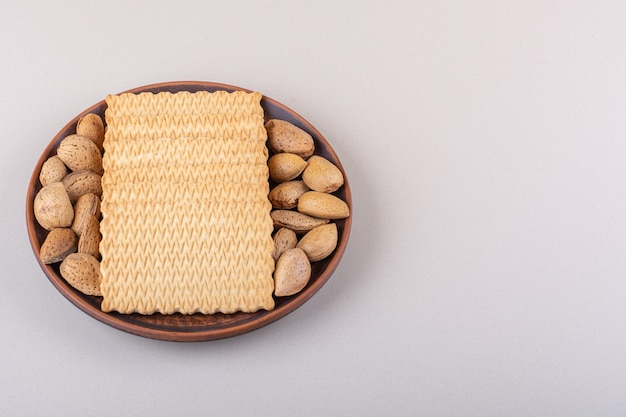 Plate of shelled organic almonds and biscuits on white background. high quality photo
