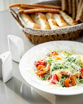 A plate of shrimp caesar salad served with bread basket, salt and pepper