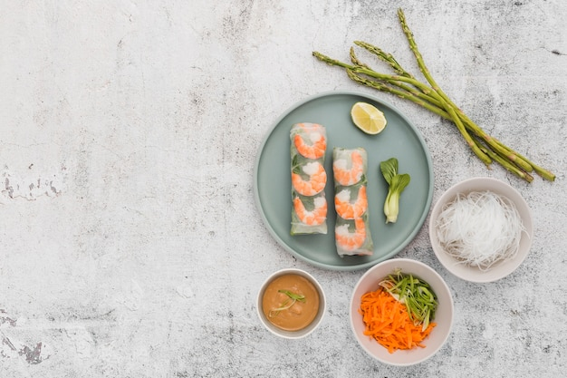 Plate of shrimp rolls with asparagus and copy space