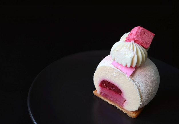 Plate of slice of strawberry vanilla mousse cake with copy space on black background