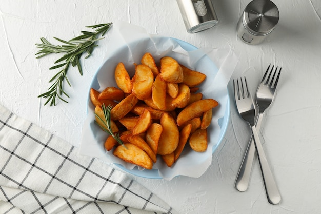 Plate of sliced baked potato wedges, rosemary, salt, forks on white, top view. closeup