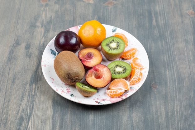 Plate of sliced fruits on wooden surface