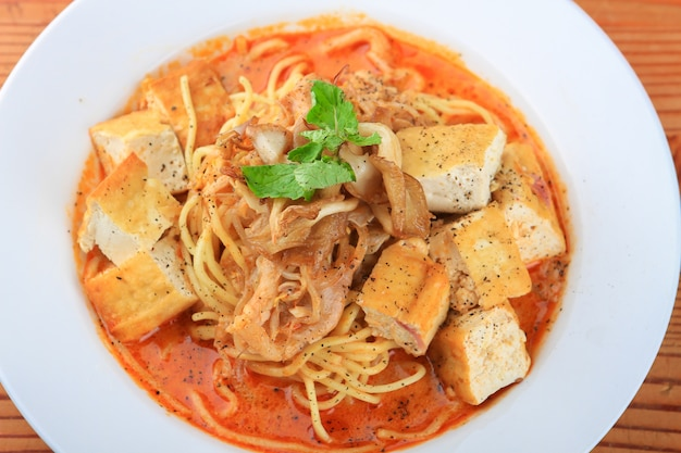 Plate of soup with spaghetti, bread pieces and decorated with greens