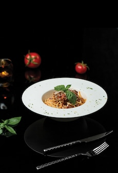 A plate of spaghetti in dark restaurant.
