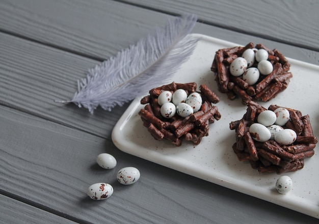 Plate of springtime chocolate nests filled with easter eggs on grey wooden table with grey decorative feather. easter sweets concept close-up