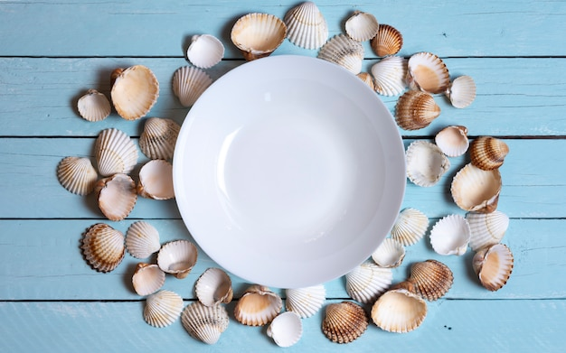 Plate surrounded by seashells with copyspace