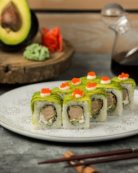 Plate of sushi rolls covered with avacado, cream and red tobiko