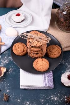 Piatto di caramelle e due torte e biscotti con cannella