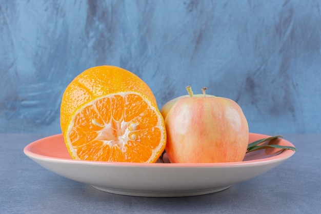 A plate of tasty apple and oranges on the dark surface