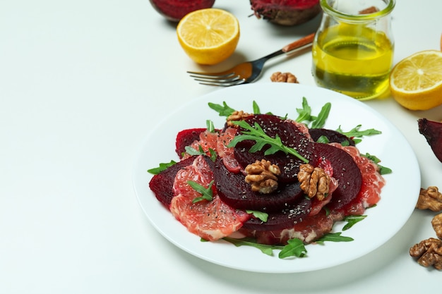 Plate of tasty beet salad and ingredients on white table