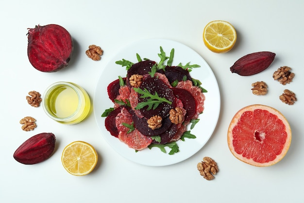 Plate of tasty beet salad and ingredients on white
