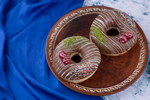 Plate of tasty chocolate donuts with sprinkles on white surface.