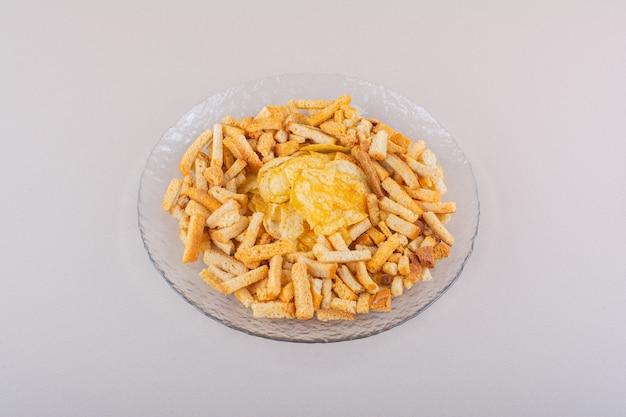 Piatto di gustosi cracker croccanti e patatine su sfondo bianco. foto di alta qualità