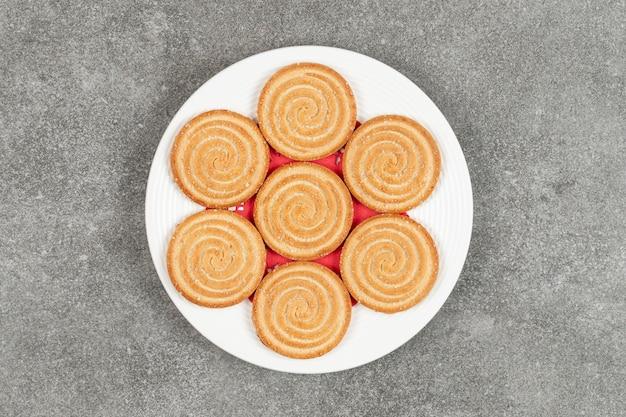Piatto di gustosi biscotti rotondi sulla superficie in marmo