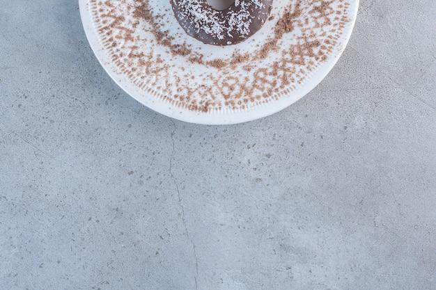 Piatto di gustosa singola ciambella al cioccolato su sfondo di pietra.