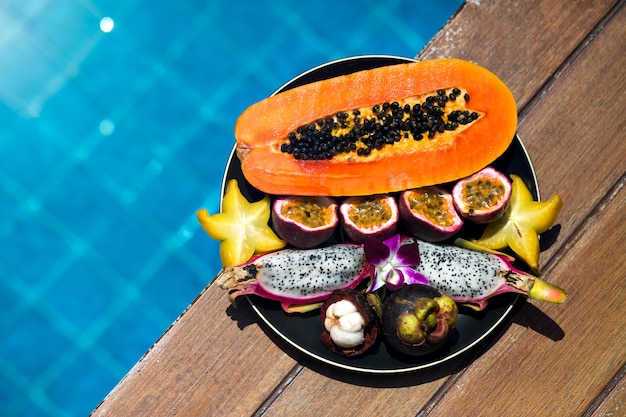 Plate of tasty sweet tropical exotic fruits stay near pool at luxury hotel, papaya, dragon fruit, mangosteen.