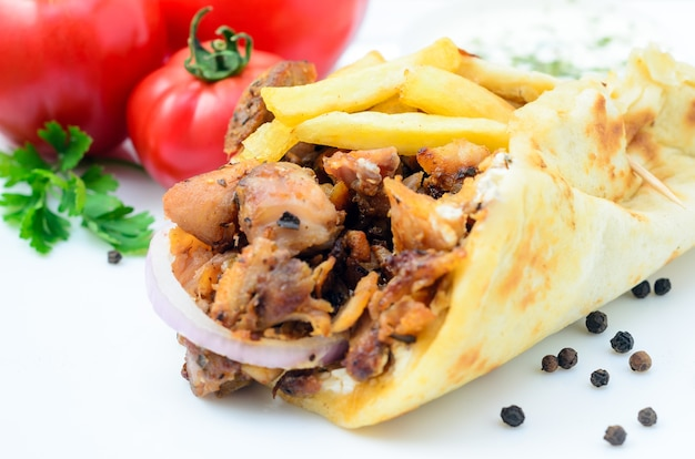 Plate of traditional greek pita gyros with meat, fried potatoes, tomato and onion