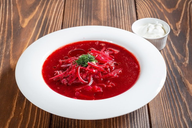 Plate of traditional russian borscht soup on wooden table