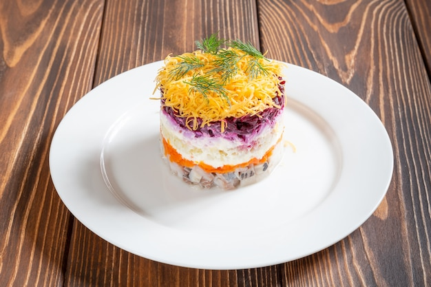 Plate of traditional russian salad called dressed herring