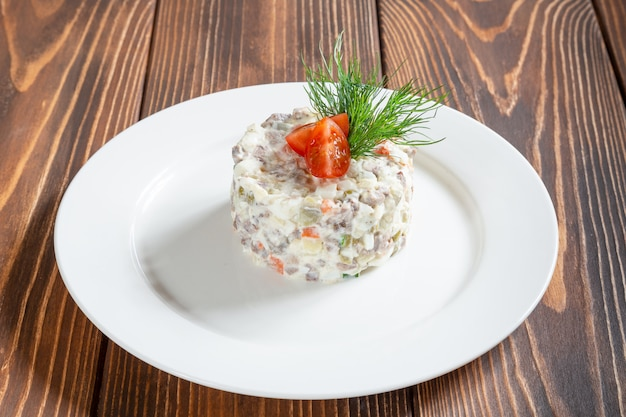 Plate of traditional russian salad olivier on wooden table